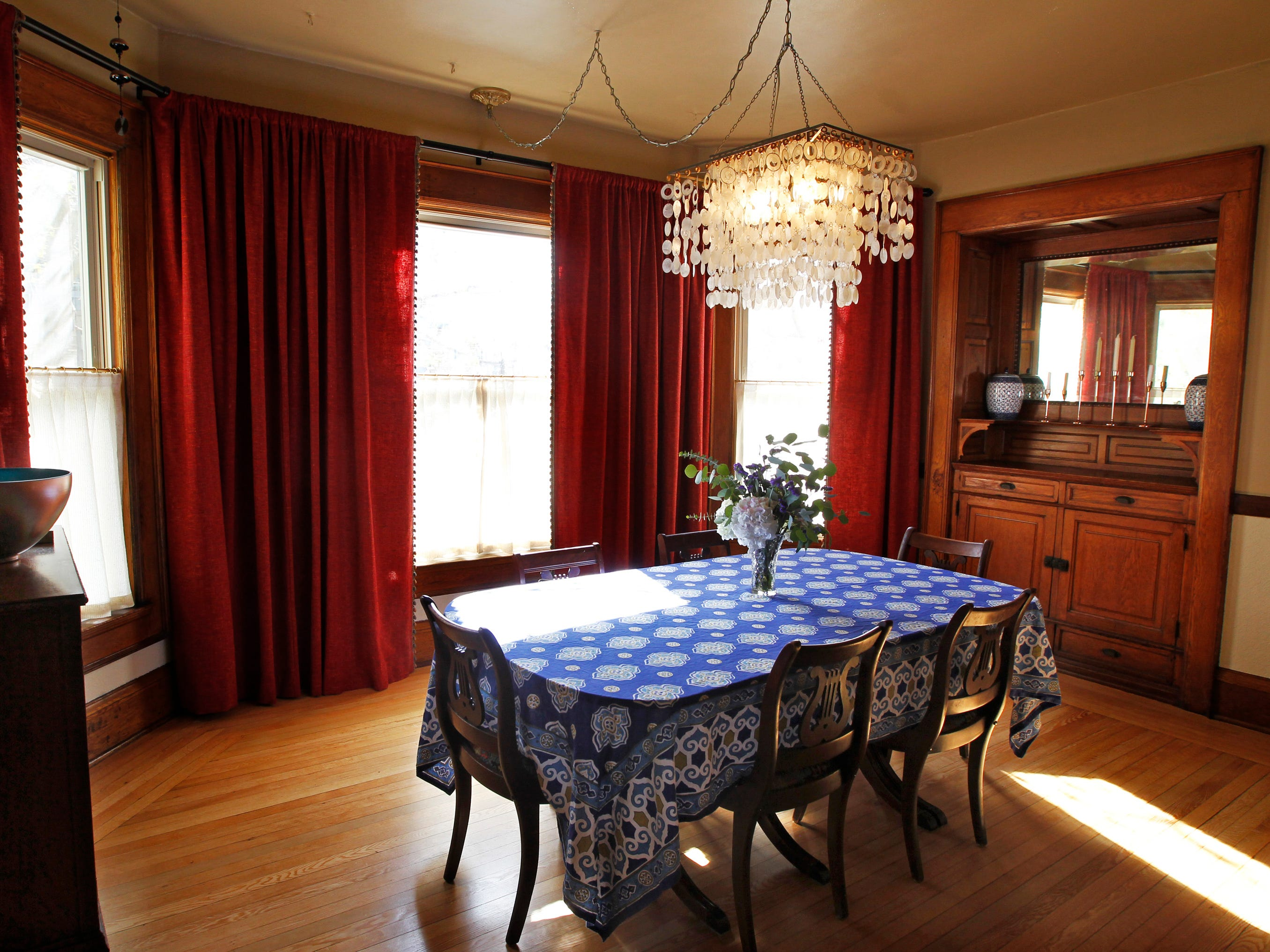The dining room has a built-in china cabinet and floor-to-ceiling windows.