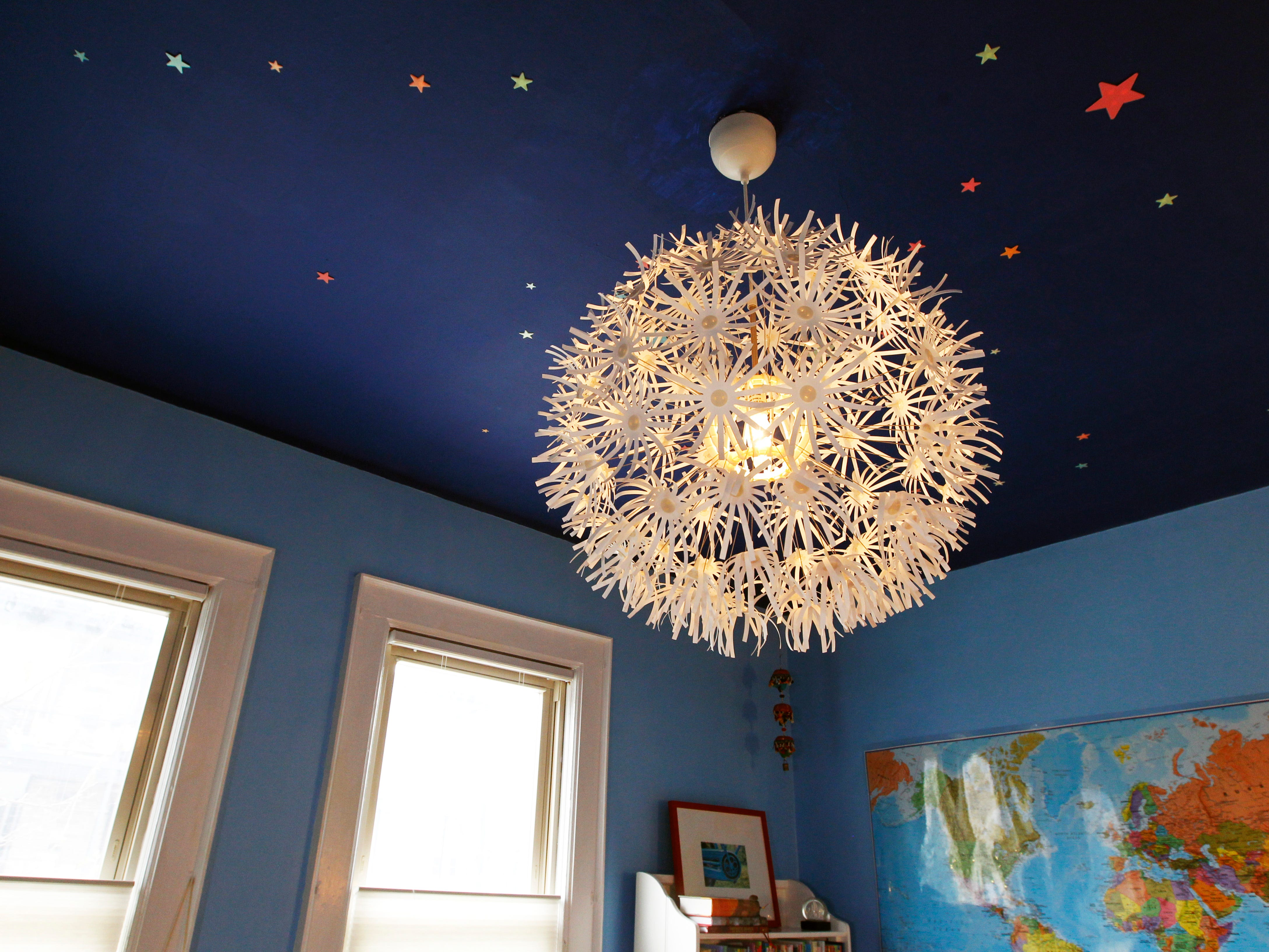 A whimsical light shade is almost moon-like as it hangs against a ceiling of stars in the Elena's bedroom.