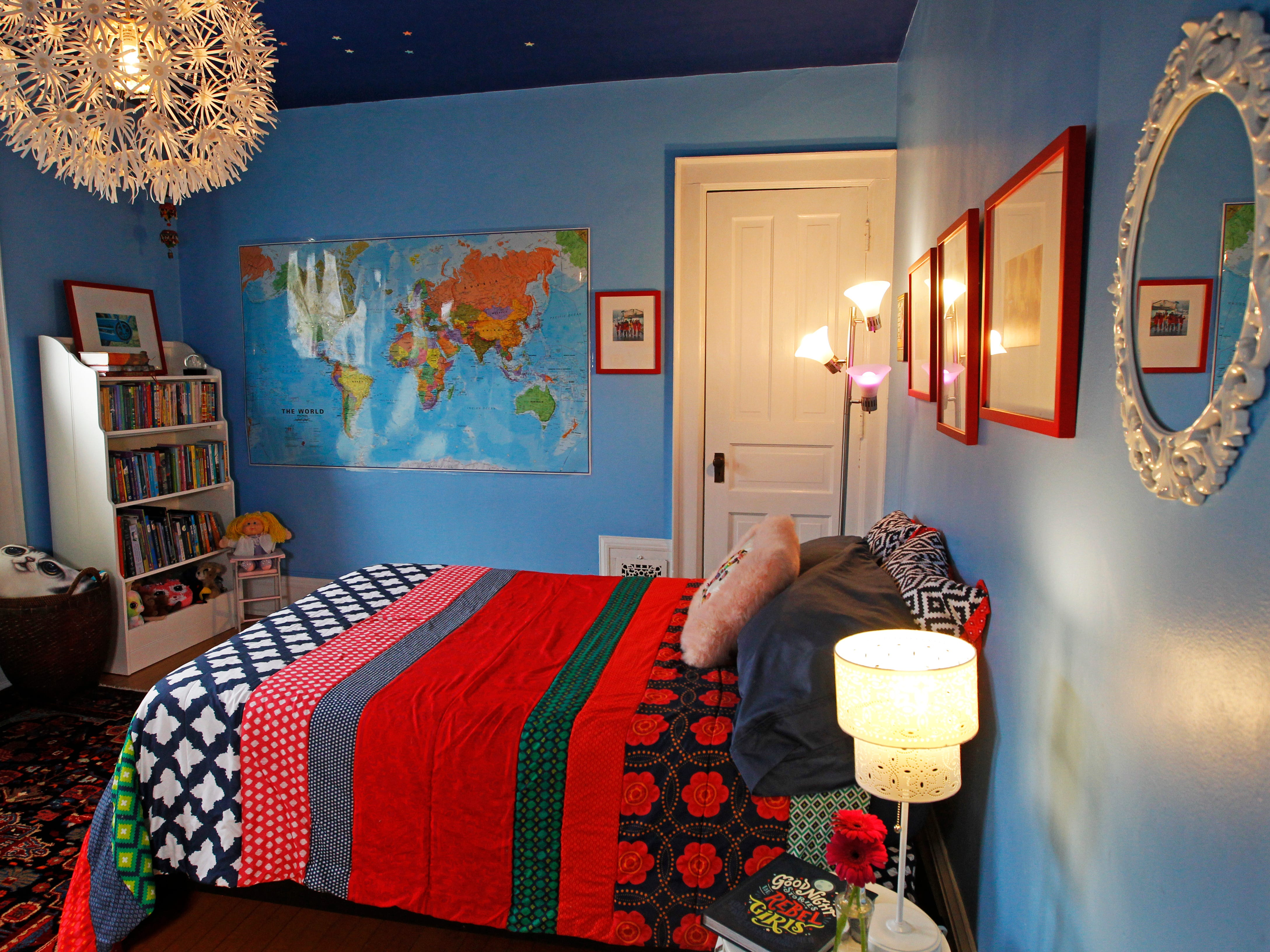 Blue colored walls, a decorative light and a mirror brighten the bedroom of 9-year-old Elena.