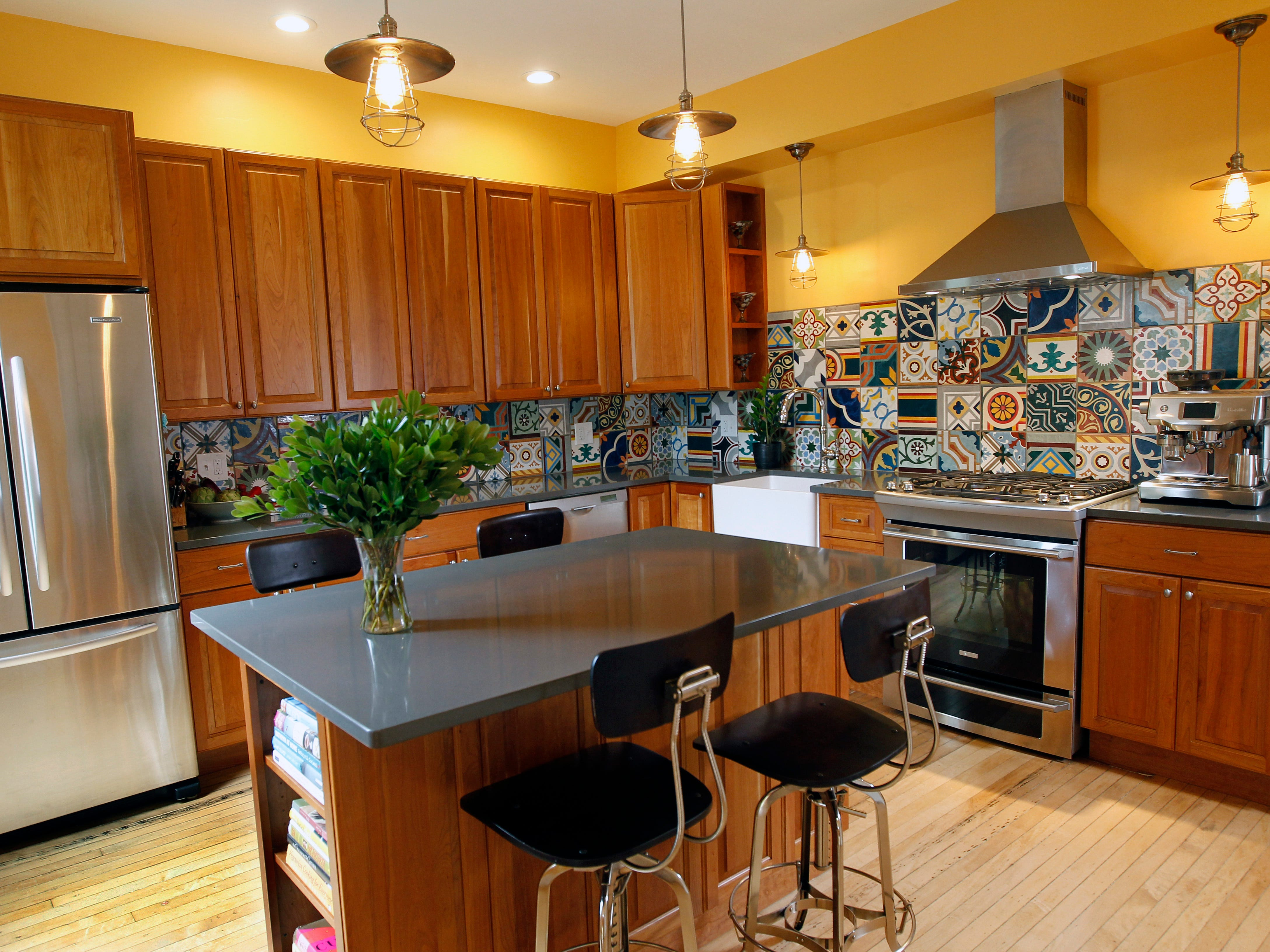 The completely redone kitchen features a quartz countertop island, pendant lighting and colorful tiles with a quilt-like pattern.
