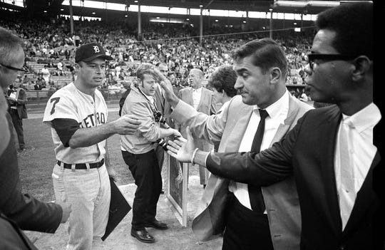 Eddie Mathews reaches out to shake hands with former Braves teammates Johnny Logan and Felix Mantilla during pregame ceremonies at Milwaukee's County Stadium before a game between the Detroit Tigers and Chicago White Sox on Aug. 26, 1968.