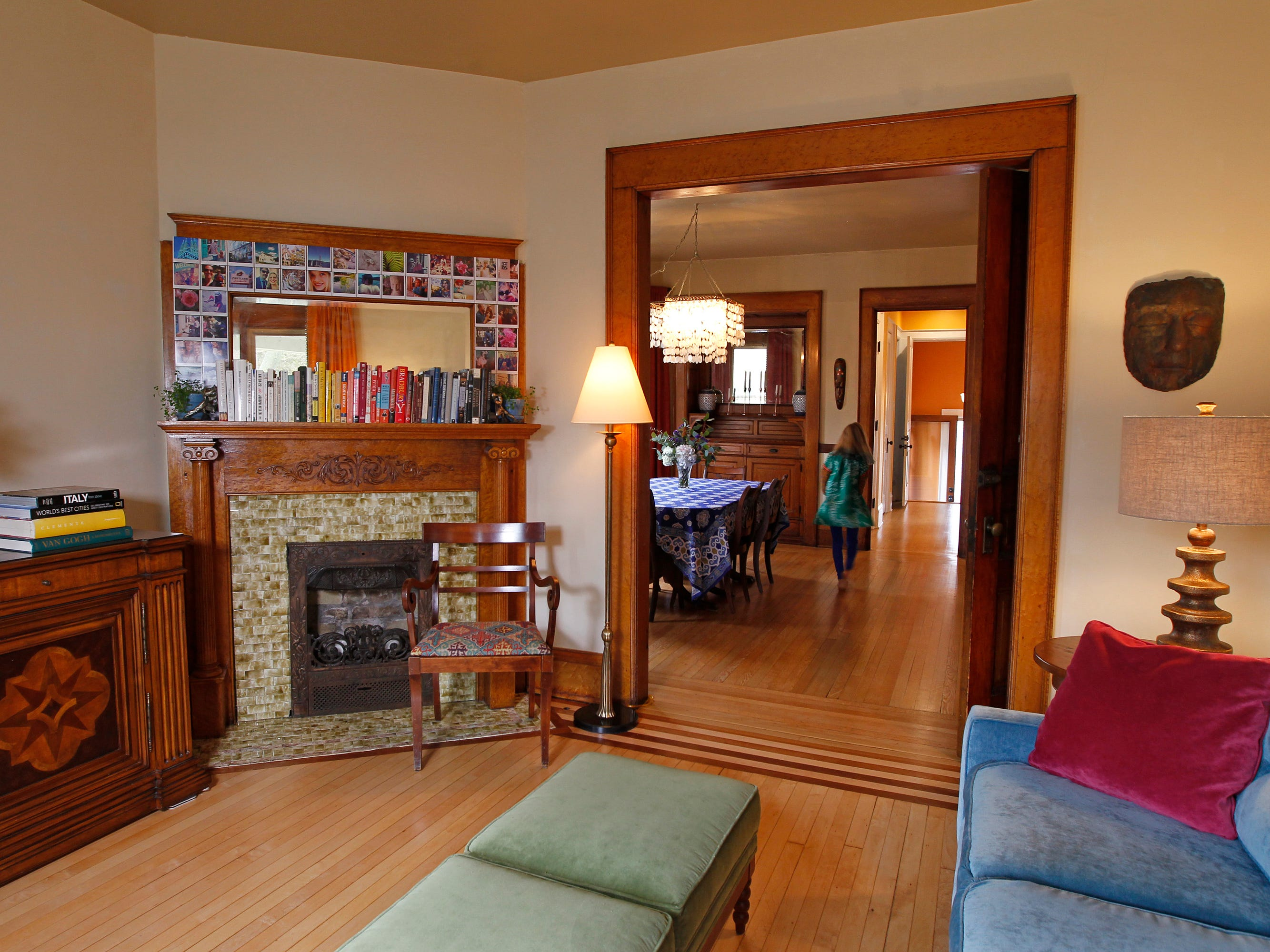 Elena, daughter of Kevin Kriehn and Mara Duckens, walks through the dining room. In the foreground is the living room with colorful furnishings. The fireplace mirror has been decorated with family photos scaled to fit the area.
