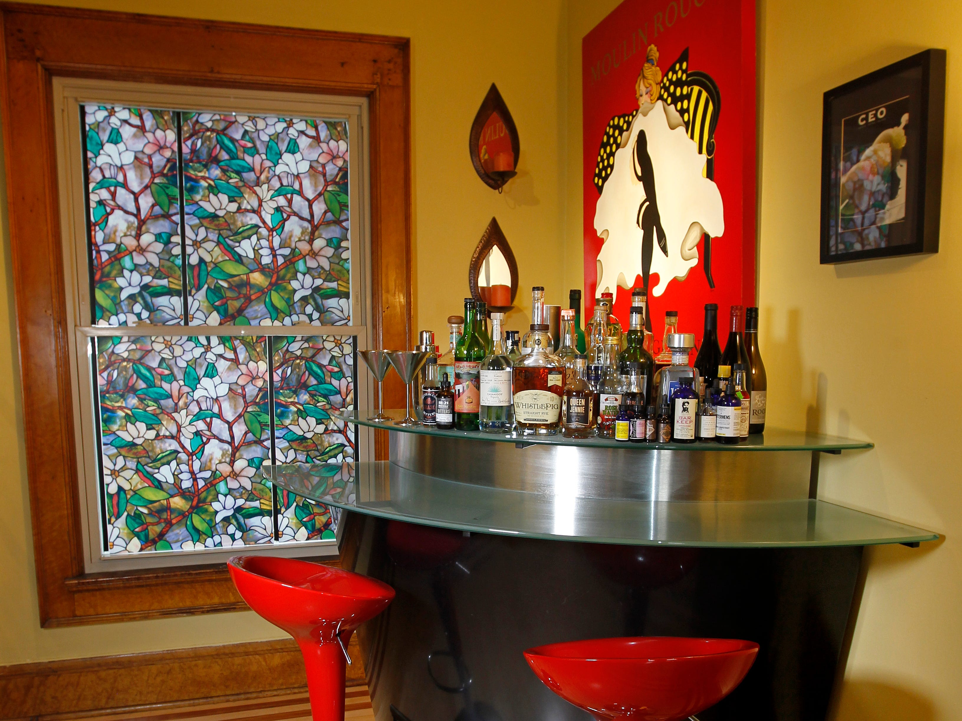 Bright red bar stools coordinate with a Moulin Rouge canvas painting in the bar area.  A faux stained glass offers a colorful accent near the modern bar made of chrome and frosted glass.