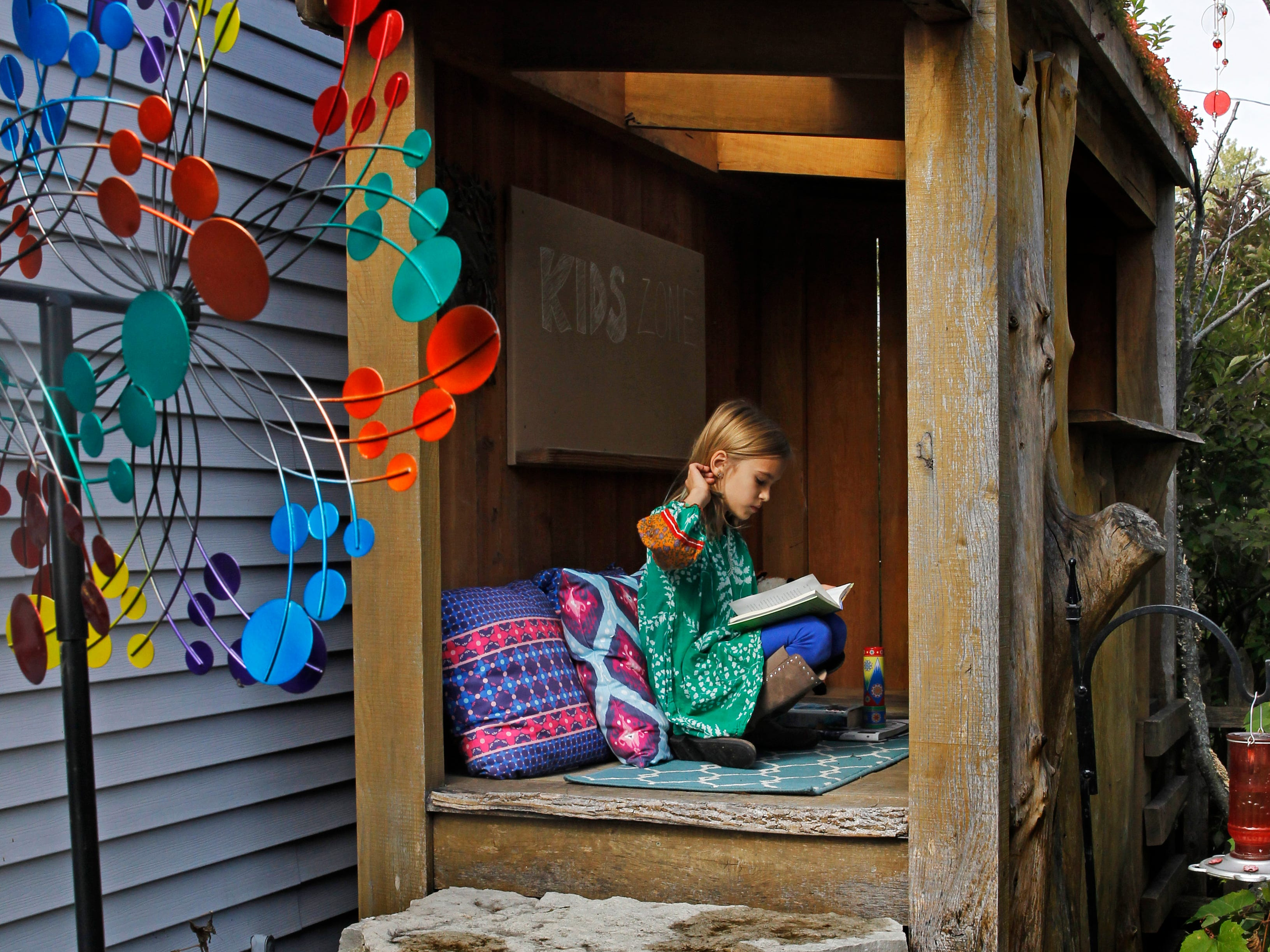 Elena, 9, reads in her natural playscape  in the backyard.