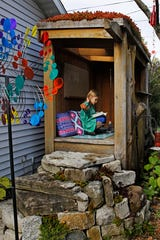 Elena, 9, reads in her natural playscape in the backyard of her parents' east side home.