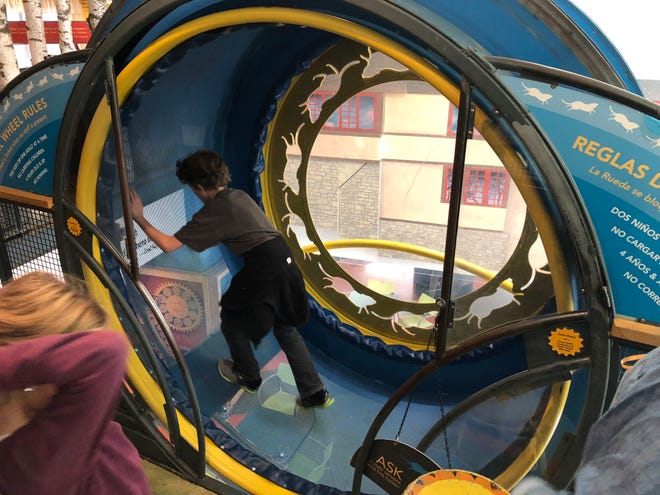 """A youngster runs in a human-sized gerbil wheel in the """"Possible-opolis"""" exhibit at the Madison Children's Museum."""