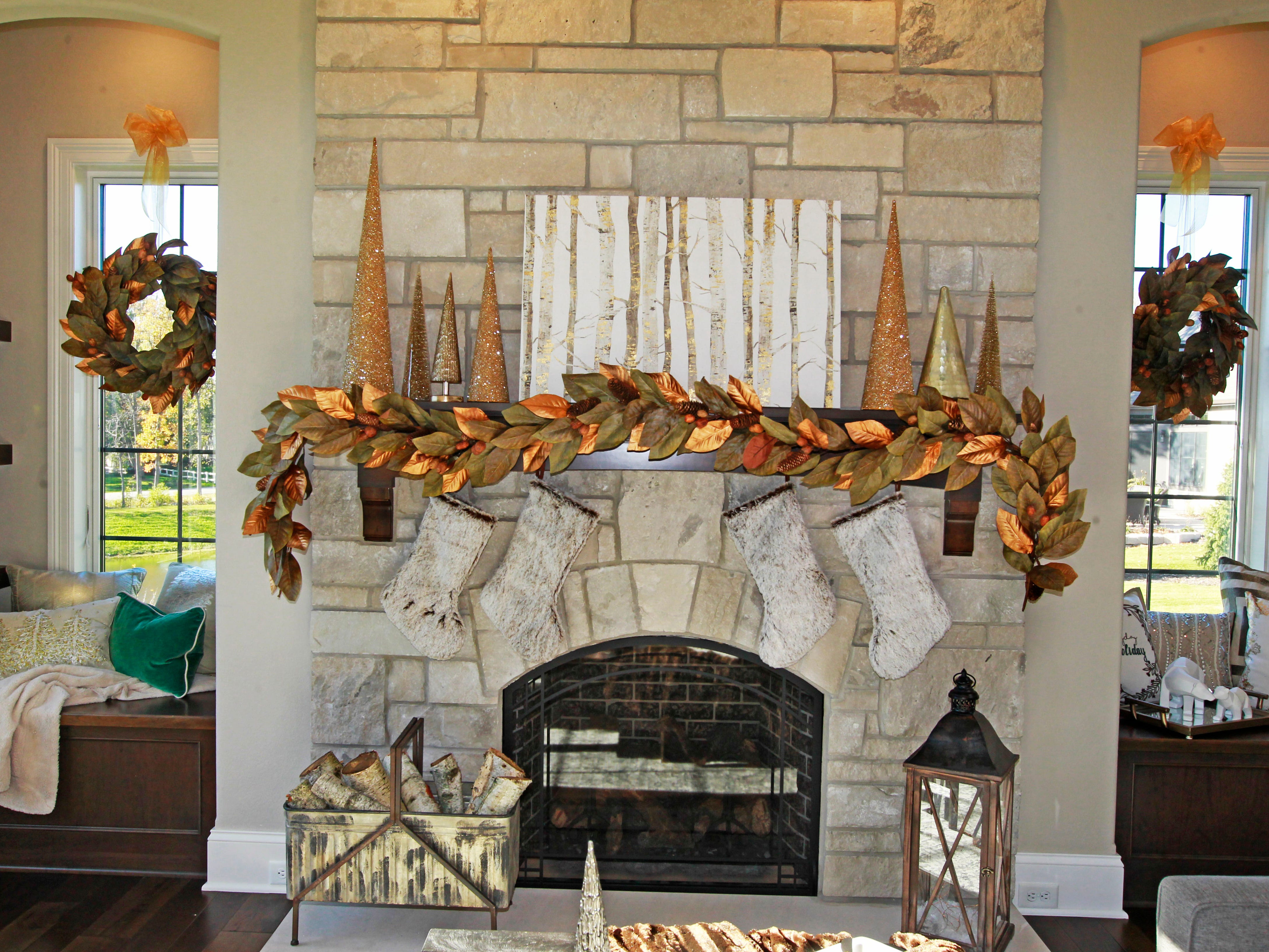 Matching wreaths hang on windows on both sides of the fireplace.