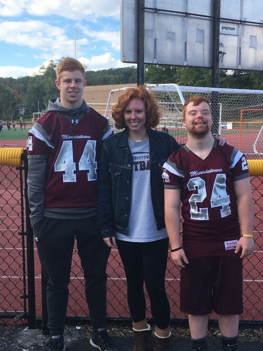 Siblings Eric, Casey and Kevin Hasenbein celebrate following Morristown's football game against Delbarton on Saturday.