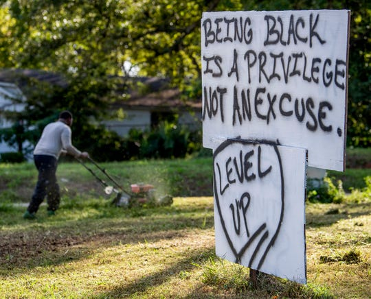 Cedric Sanders mows grass by a sign he painted at the corner of South Hull Street and Mill Street in Montgomery, Ala. on Monday October 22, 2018. Sanders is opening a pizza place near the intersection.