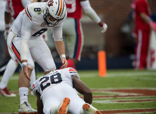 Auburn's Jarrett Stidham (8) helps up Auburn's JaTarvious Whitlow (28) after Whitlow fumbled on the one-yard line at Vaught-Hemingway Stadium in Oxford, Miss., on Saturday, Oct. 20, 2018. Auburn defeated Ole Miss 31-16.
