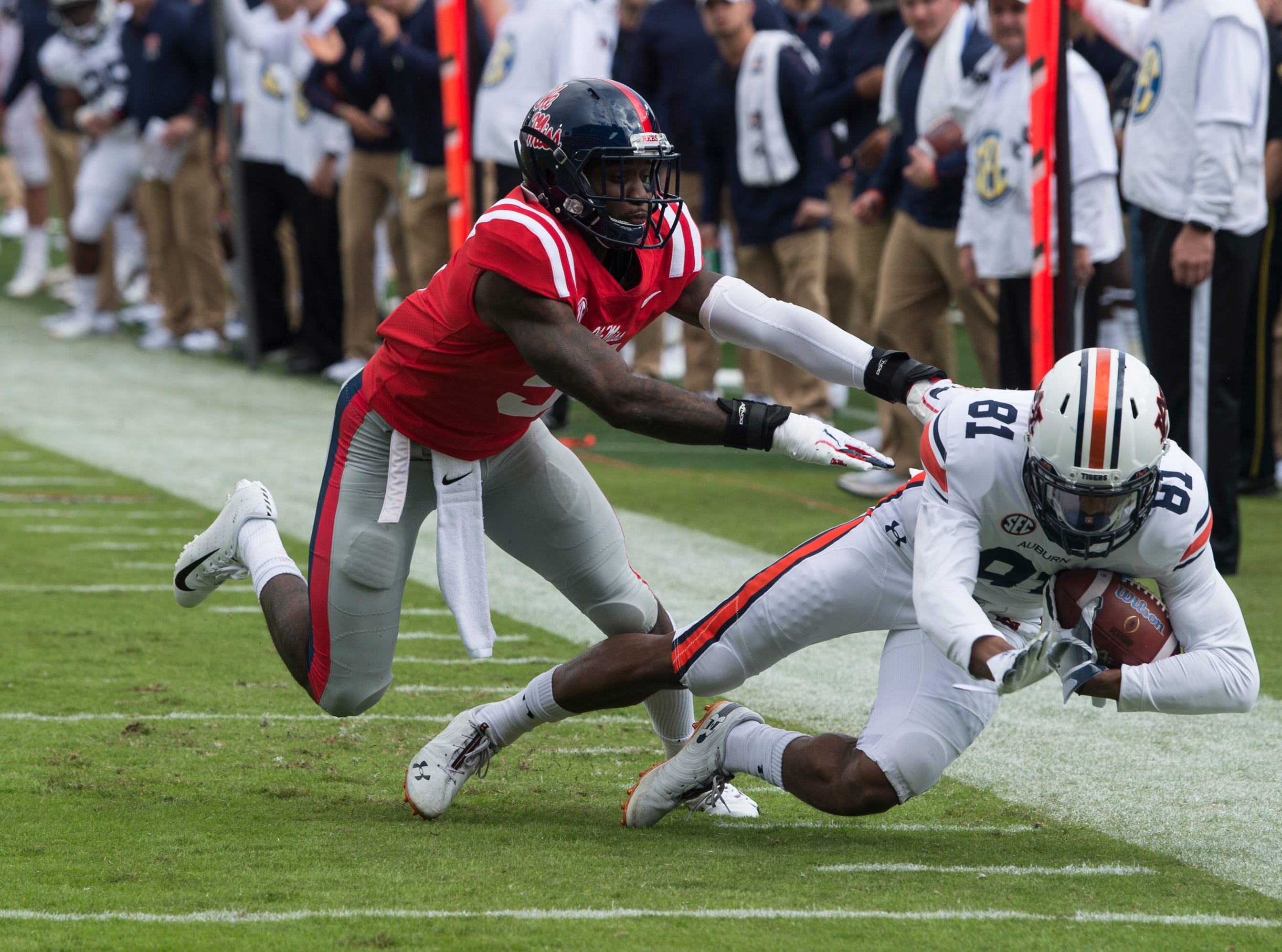 Auburn's Darius Slayton (81) is tackled by Ole Miss' Ken Webster (5) at Vaught-Hemingway Stadium in Oxford, Miss., on Saturday, Oct. 20, 2018. Auburn defeated Ole Miss 31-16.