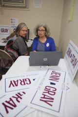 Democrat Jenn Gray, right, explains phone banking to a campaign volunteer.