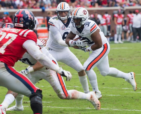 Auburn's Jarrett Stidham (8) hands the ball off to Auburn's Malik Miller (32) at Vaught-Hemingway Stadium in Oxford, Miss., on Saturday, Oct. 20, 2018. Auburn defeated Ole Miss 31-16.