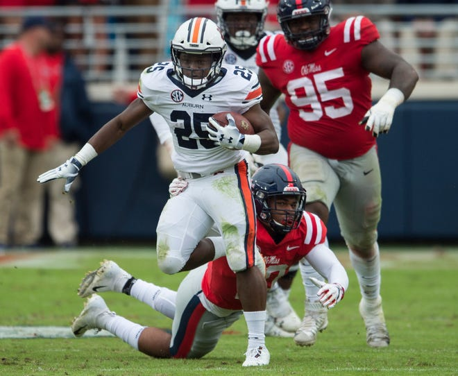 Auburn's Shaun Shivers (25) is tripped up by Ole Miss' Jacquez Jones (10) at Vaught-Hemingway Stadium in Oxford, Miss., on Saturday, Oct. 20, 2018. Auburn defeated Ole Miss 31-16.