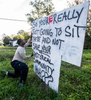 Cedric Sanders checks on his sign as he works on it at the corner of South Hull Street and Mill Street in Montgomery, Ala. on Monday October 22, 2018. Sanders is opening a pizza place near the intersection.