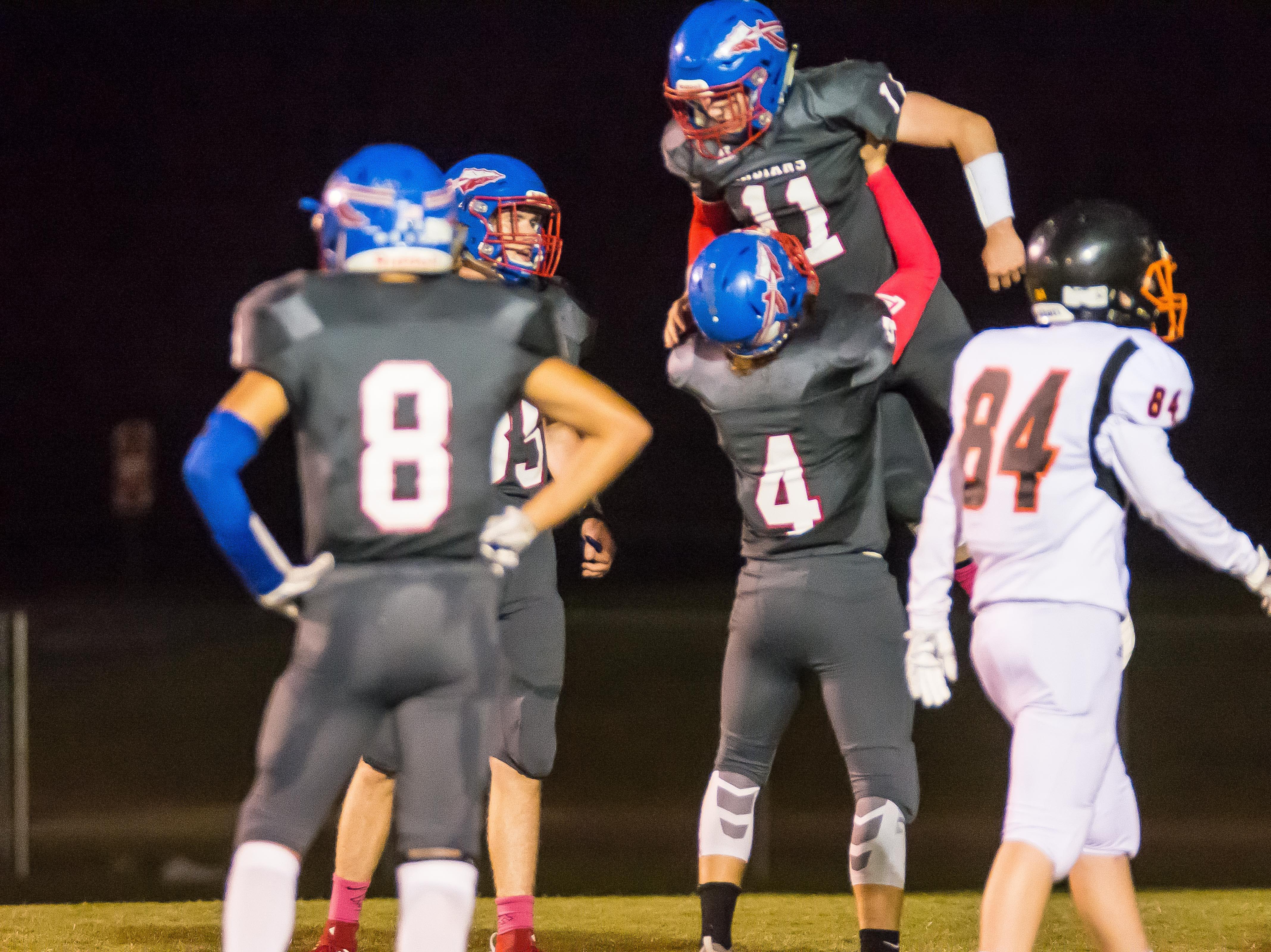 Harpeth's Justen Utley lifts up Luke Gossett after one of Gossett's five touchdowns against Fayetteville.