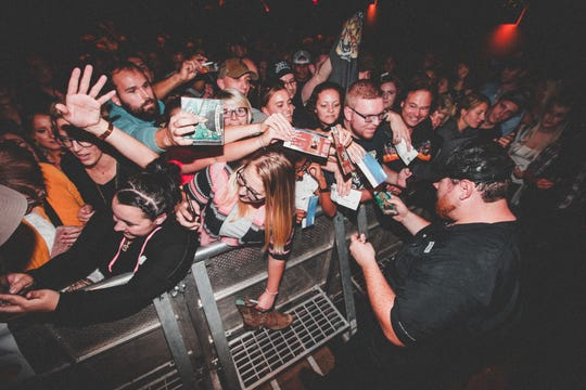 Luke Combs signs autographs for fans after a show in Berlin on Oct. 11.