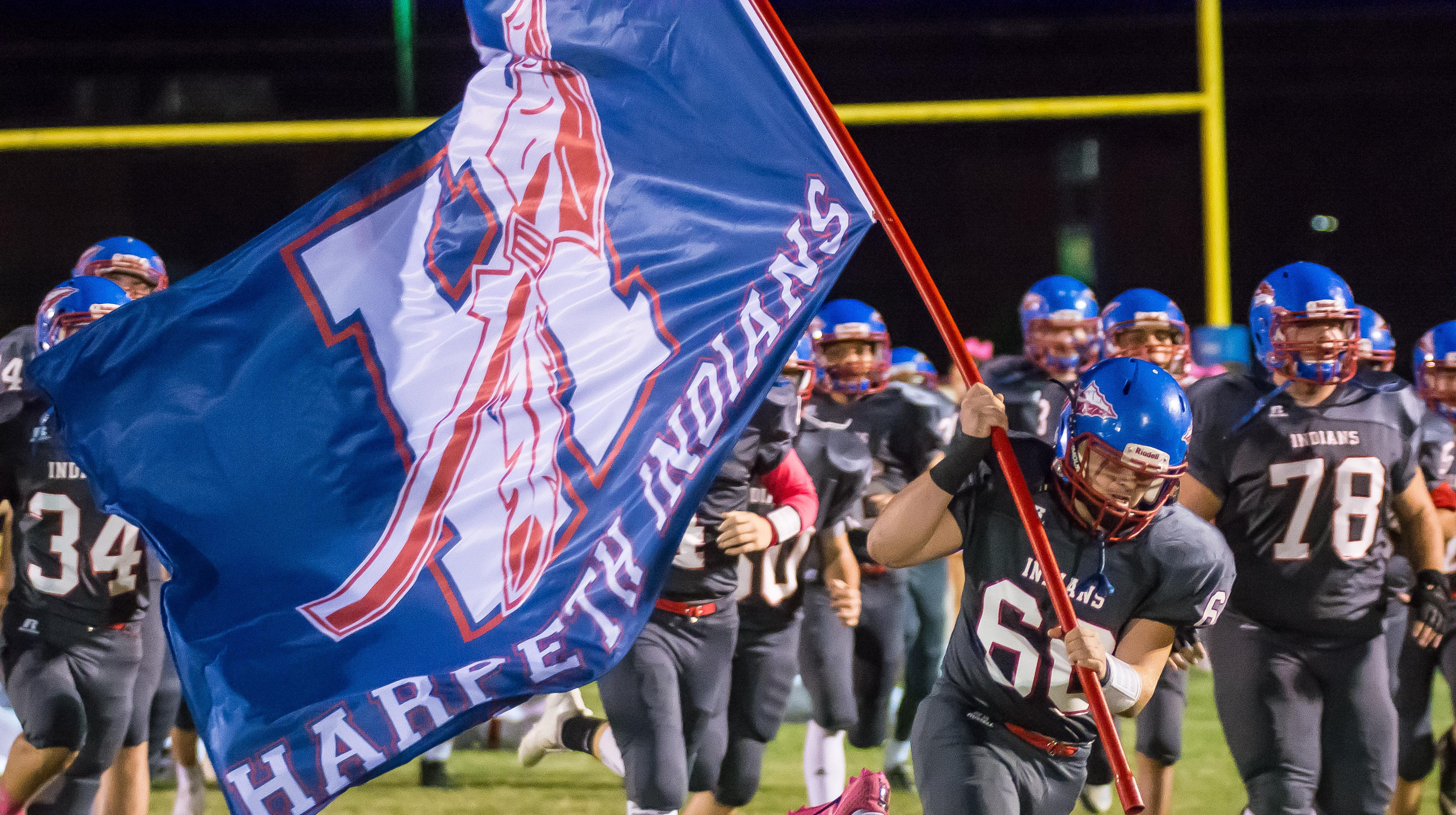 Harpeth's Logan Calies carries the Harpeth flag...