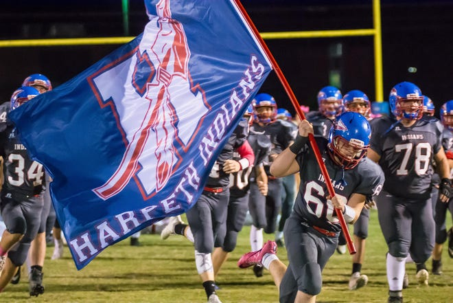 Harpeth's Logan Calies carries the Harpeth flag before the Indians game with Fayetteville.