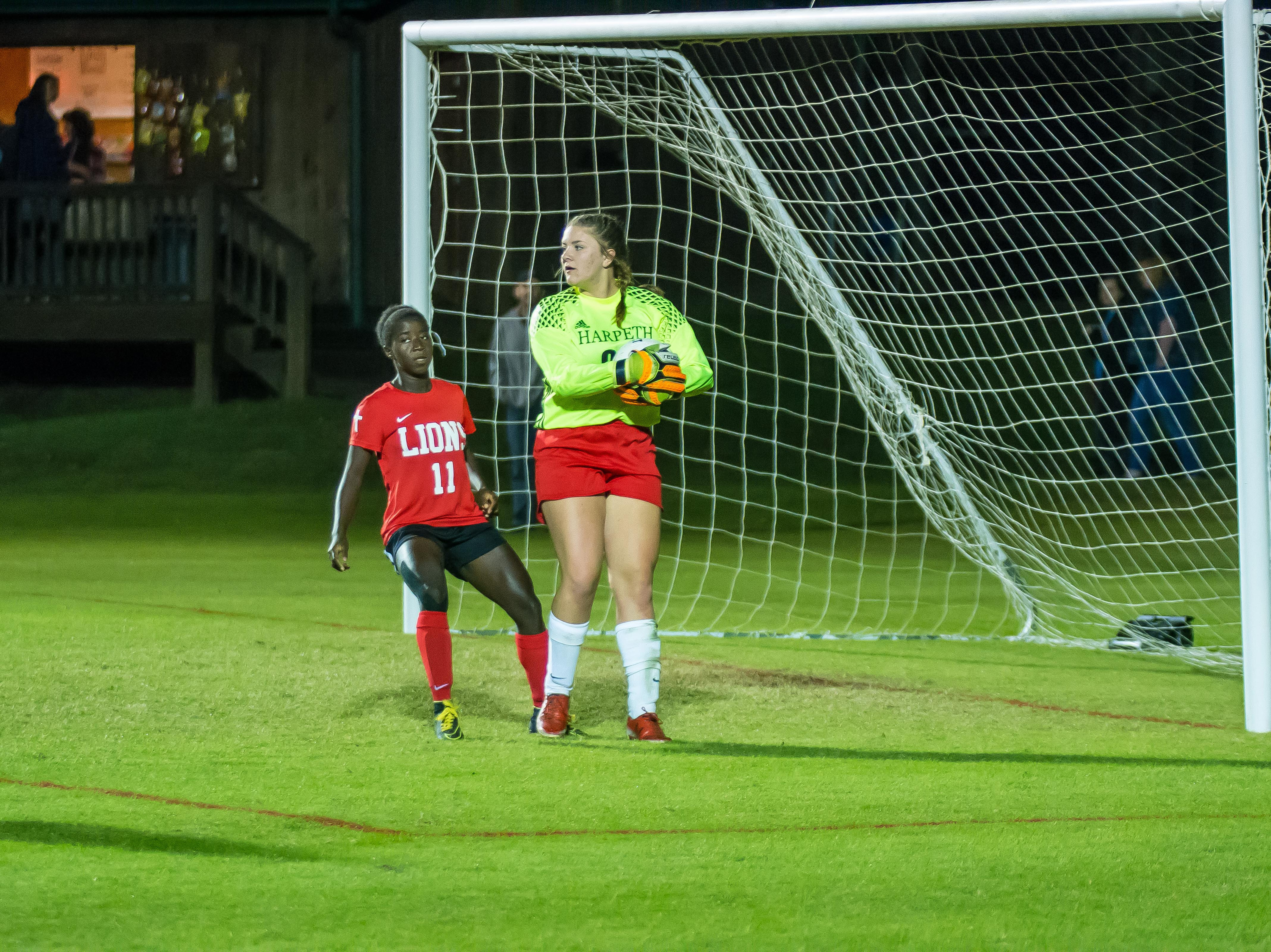 Harpeth goalkeeper Emelia Hurt takes one away from reigon tournament MVP Gabby Jones.