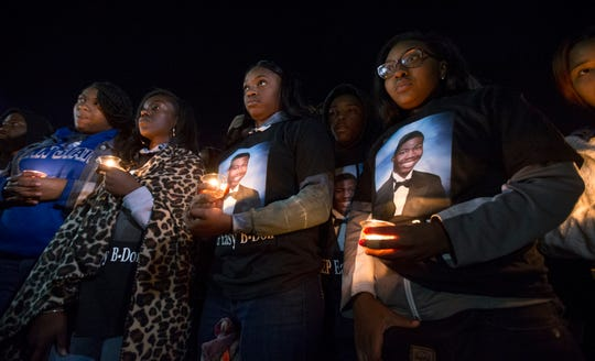 Friends hold candles during a vigil held  Sunday, Oct. 21, 2018, to remember Brandon Adams who was shot and killed in the parking lot of McGavock High School, in Nashville, Tenn.