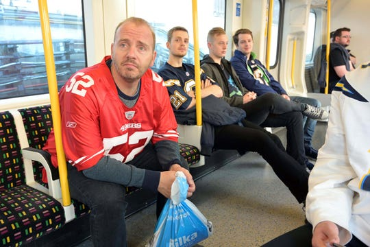 Fans wearing the jerseys of San Francisco 49ers linebacker Patrick Willis (52) and San Diego Chargers running back LaDainian Tomlinson (21) ride the Metropolitan Underground line to the game Sunday.
