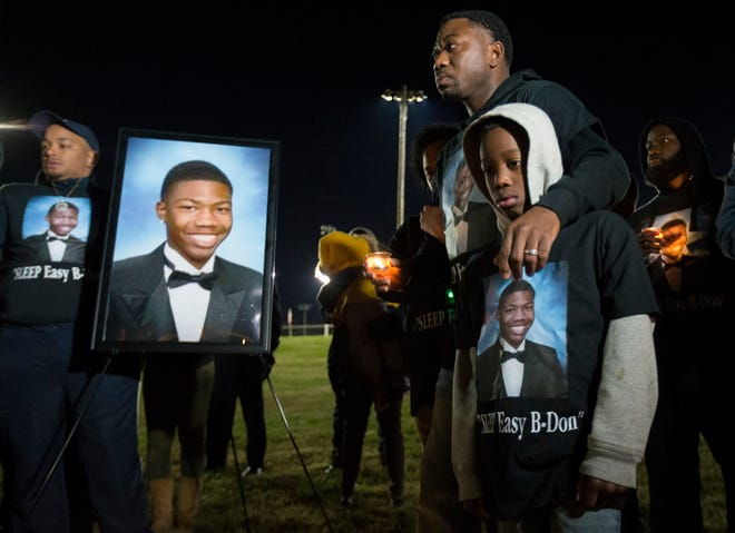Juan Adams, father of Brandon Adams, stands with his nephew, Keori Brooks during a vigil Sunday, Oct. 21, 2018, held to remember Brandon who was shot and killed in the parking lot of McGavock High School, in Nashville, Tenn.
