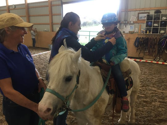 """Riding her """"best buddy"""" Stormy, Layla Messerall receives a ribbon after her Oct. 20 ride from Laura Siddens, while Susan Ginise looks on."""