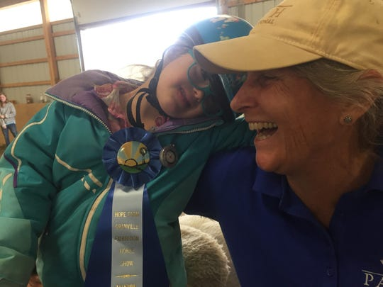 Layla celebrates completion of her ride and ribbon award with Susan Ginise.