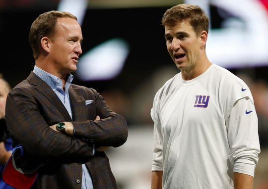 Former NFL quarterback Peyton Manning, left speaks with younger brother New York Giants quarterback Eli Manning before an NFL football game between the Atlanta Falcons and the New York Giants, Monday, Oct. 22, 2018, in Atlanta.