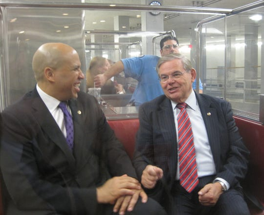 Sen. Cory Booker laughs as he and Sen. Bob Menendez ride a subway from the Capitol to the Russell Senate Office after Booker's first vote in the Senate on Oct. 31, 2013.
