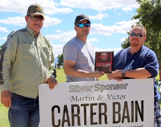From left, R.L. Stockard and Deming Police Chief Bobby Orosco presented a plaque to sponsor Victor Cabrera of Carter Bain Wealth Management