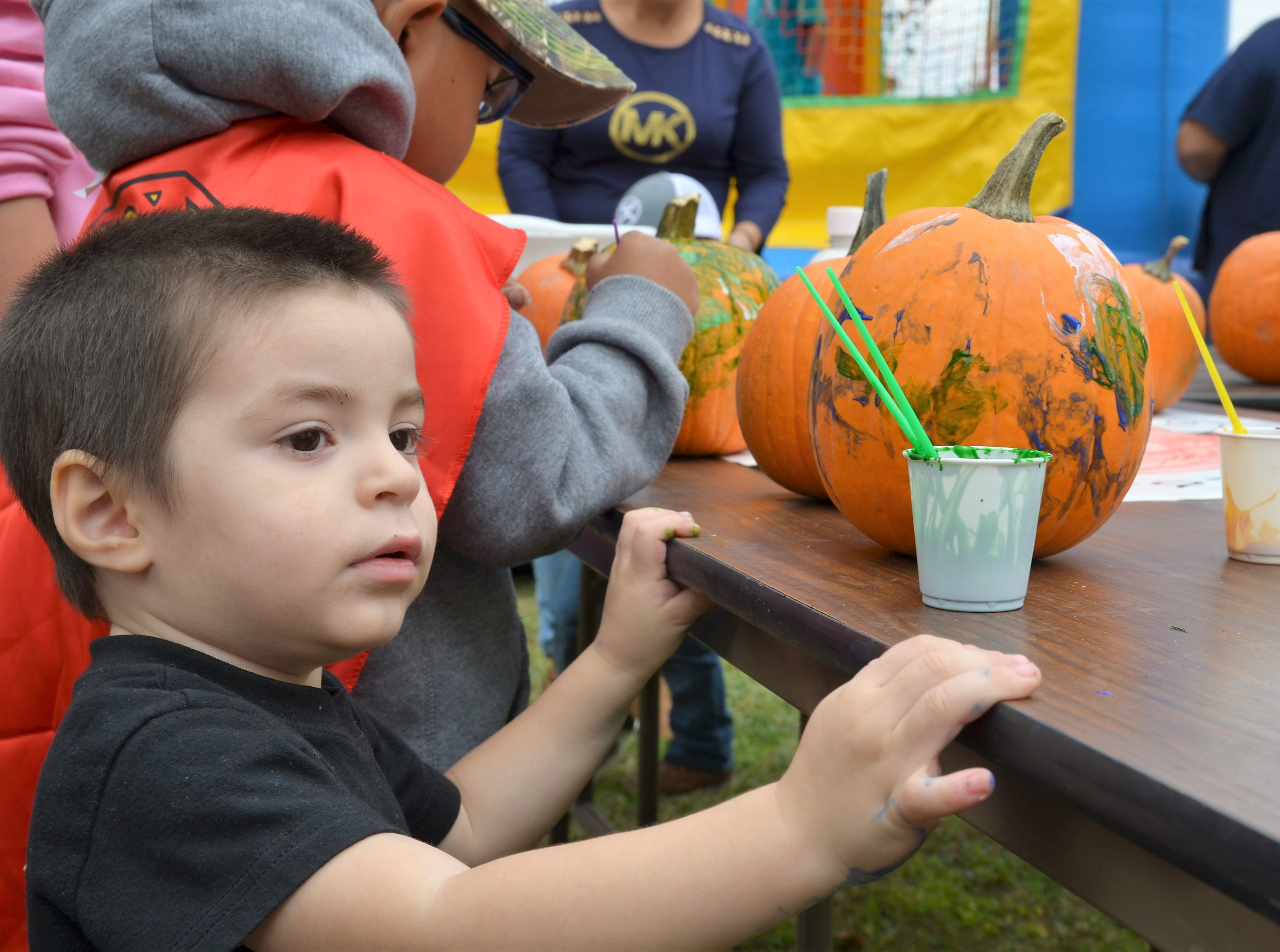 Pedro G. L. Barraza, 2, looked at other colors of paint to decorate his pumpkin. Pumpkin decorating was one of my activities during the Klobase Festival at Court House Park on Sunday.