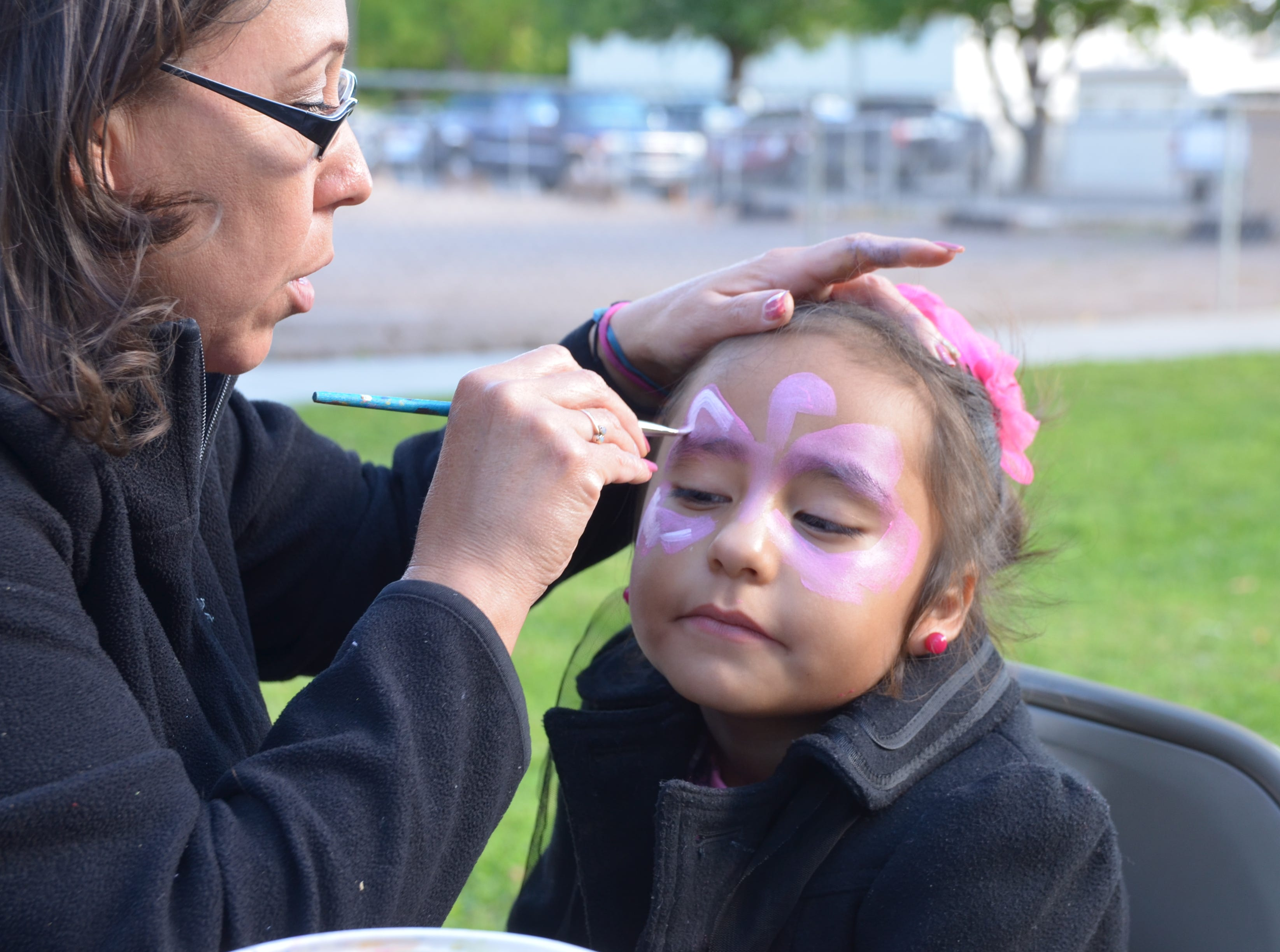 Ruby Luera, 6, got her face painted as a flamingo during the 90th annual Klobase Festival at Courthouse Park on Sunday.