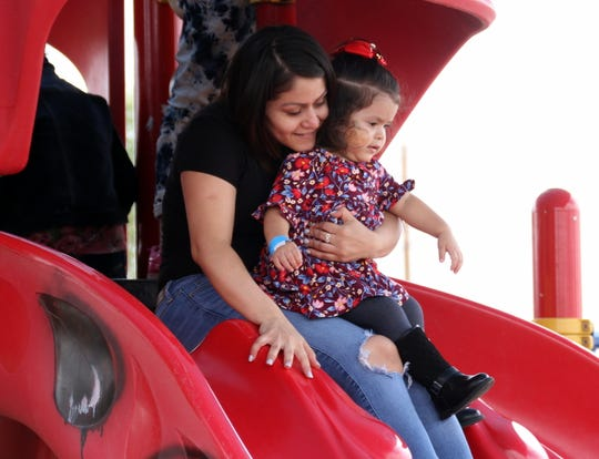 Karyme Morales, 2, headed down the playground slide with her mother, Alondra, at John T. Waits (Rabbit) Park.