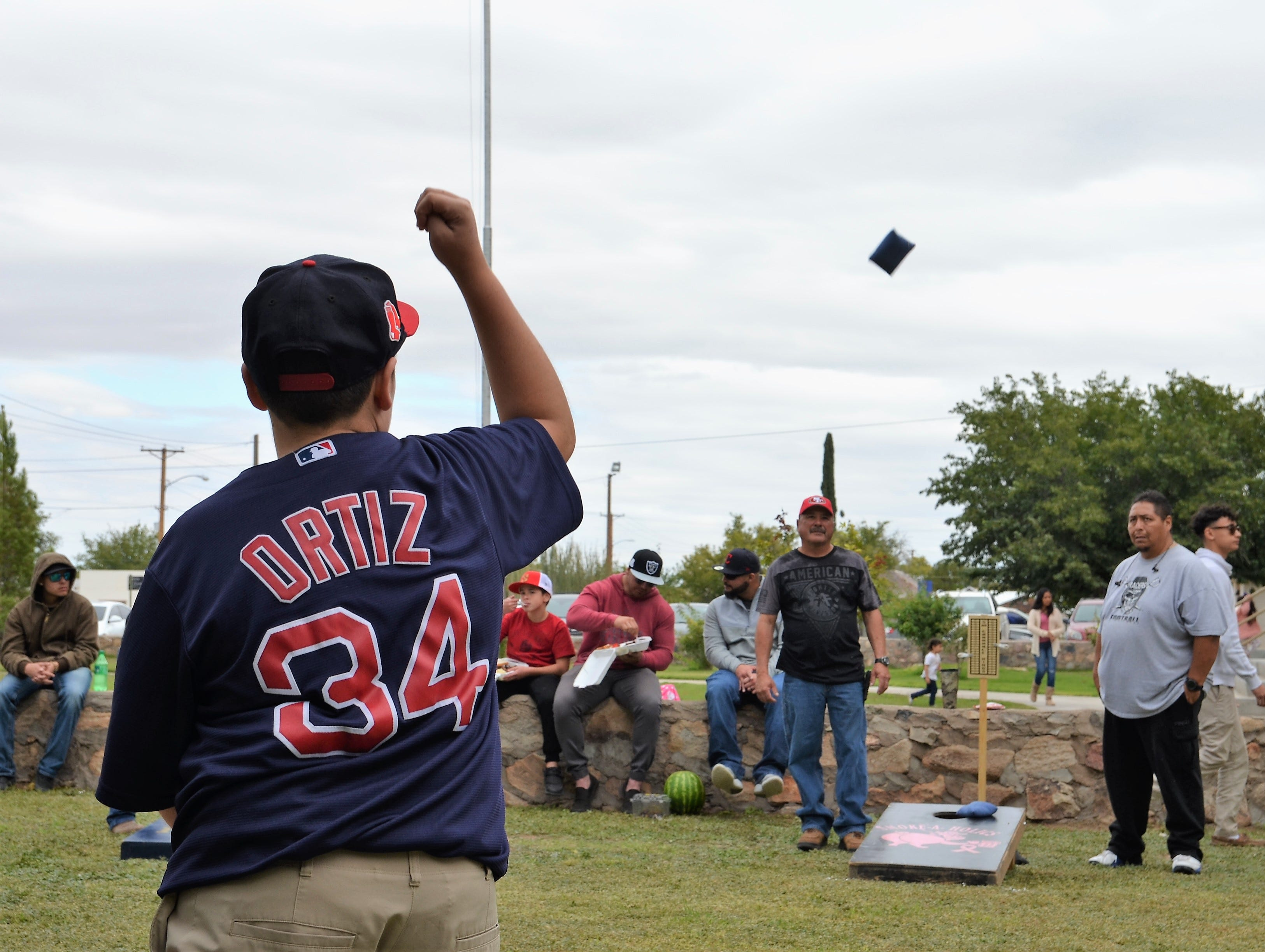 Javier Gallosa, 14, throws a bean bag while playing corn hole toss with his family members, including his dad at right: Javier Gallosa during the Klobase Festival Sunday.