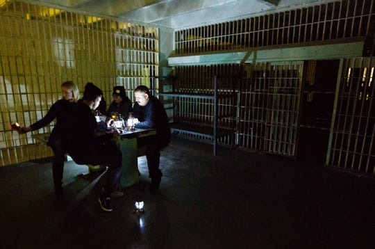 Las Cruces Sun-News freelance reporter Cassie McClure, left, sits with her team while using an electromagnetic ghost detector during a paranormal investigation tour offered by Backhand Entertainment at the abandoned Doña Ana County Courthouse.