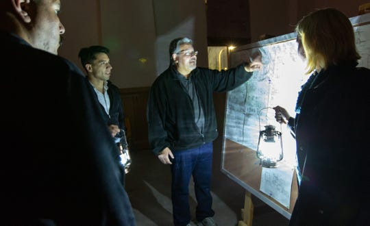 Backhand Entertainment's David Crider explains locations on various maps of the abandoned Doña Ana County Courthouse on Thursday, Oct. 18, during a paranormal investigation tour.
