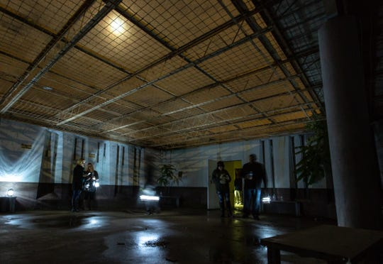 Las Cruces Sun-News freelance reporter Cassie McClure and her team investigate the courtyard during a paranormal tour offered by Backhand Entertainment at the abandoned Doña Ana County Courthouse on Thursday, Oct. 18.