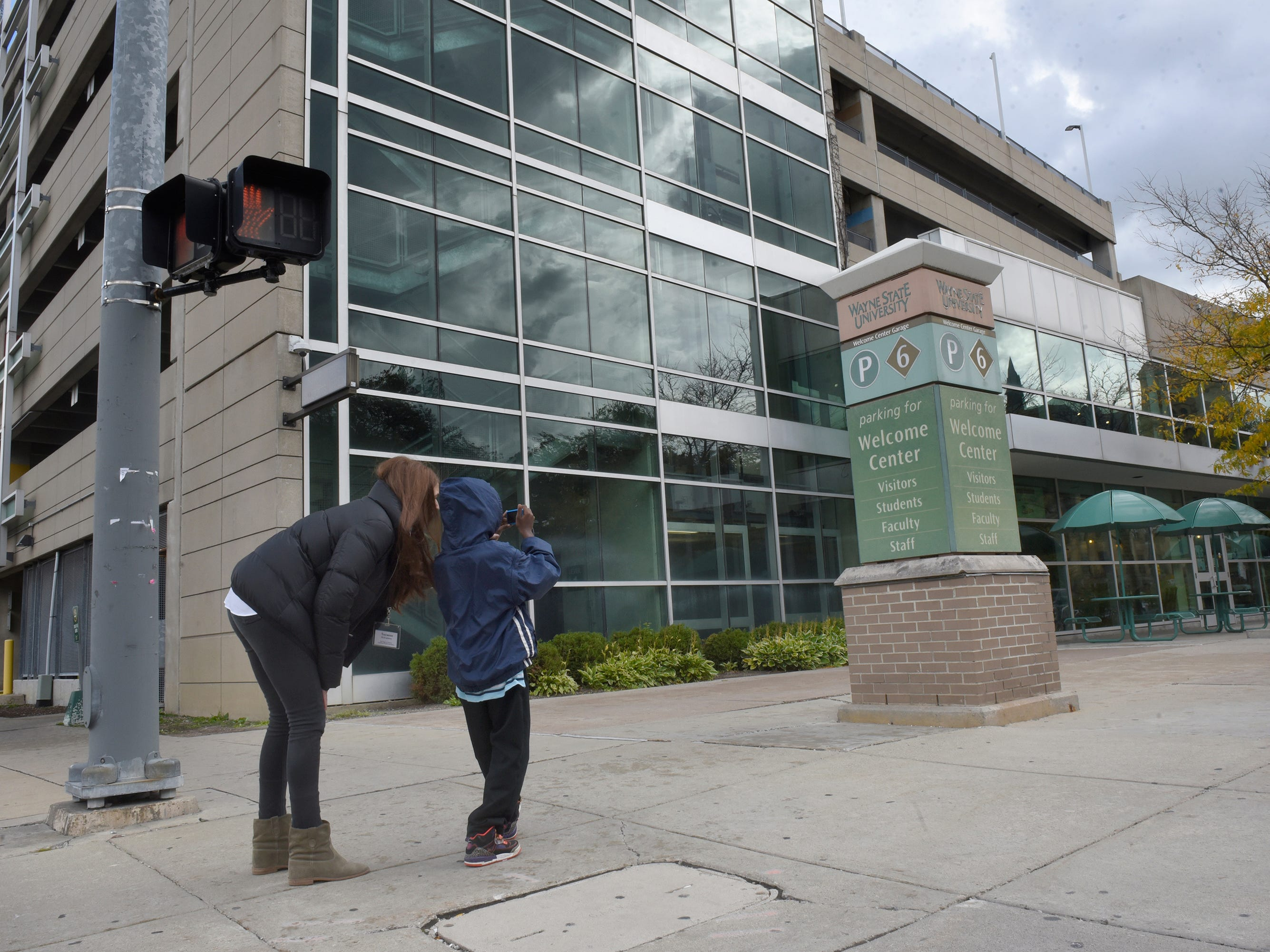 Suzanne McEachern helps Ethan photograph a sign at Wayne State University.
