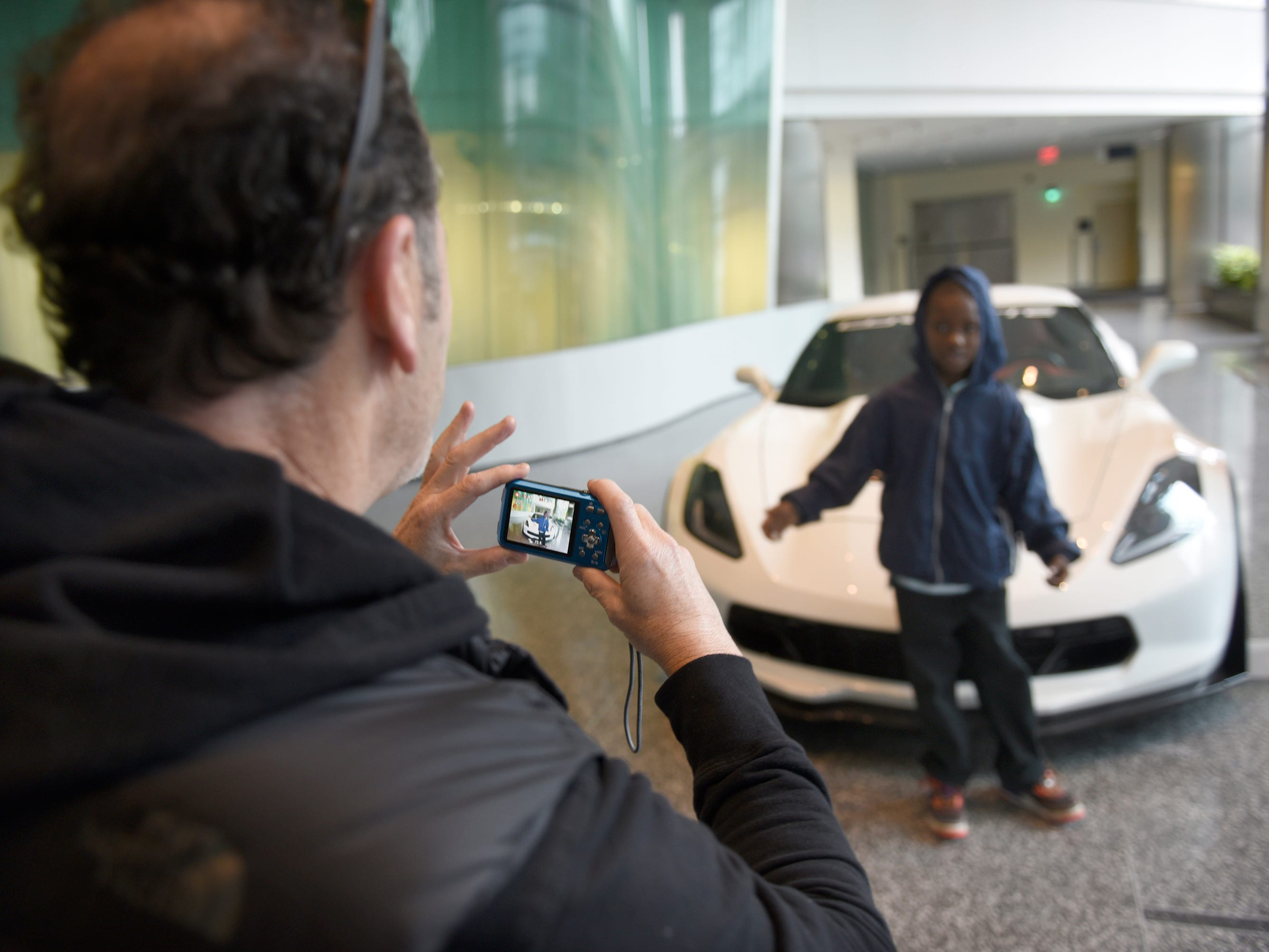 Gaal Karp takes a photo of Ethan as he poses in front of a Corvette at the Ren Cen in Detroit.