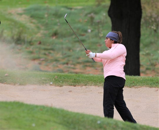 Northville's Sufna Gill draws an iron out of the sand trap at the state girls golf finals.