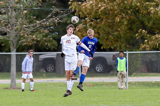 Going up simultaneously to get the ball are Canton's Nick Provenzano (20) and Salem's Josh Pohl (11).