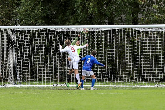 Salem senior goalkeeper Buraq Oral jumps up to snag a ball, with Canton's Lon Scheffler (9) and Salem's Nolan Chaput (3) on the doorstep.