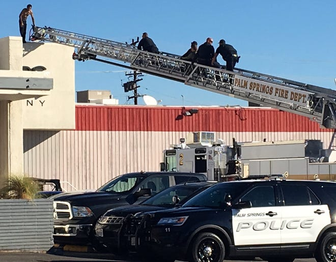 Police climb a fire ladder to speak to a shirtless man who climbed atop the roof of a business on Monday morning, Oct. 22, 2018. It was not clear why the man was on the roof.