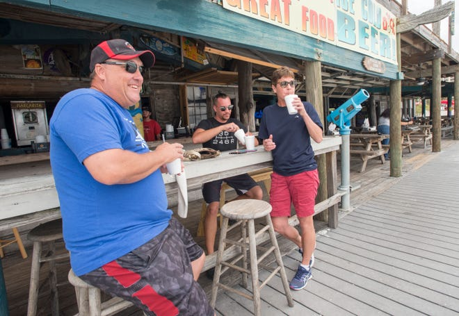 From left, Mark Meyer, Jeremy Bolden and Mary Meyer of Cincinnati relax Monday at The Dock along Pensacola Beach.