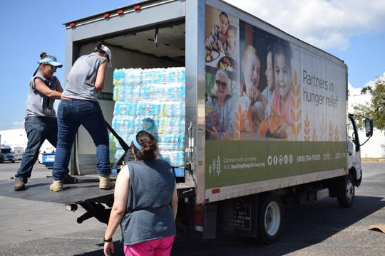 Volunteers load truckloads of water to be delivered to people in need in areas hit hard by Hurricane Michael.