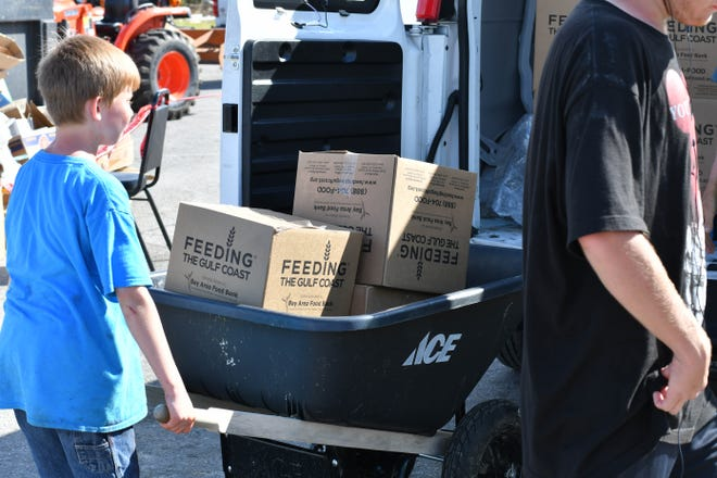 A volunteer helps deliver food in Panama City from Feeding the Gulf Coast, which is dedicating resources for long-term food relief in the hard-hit Bay County.