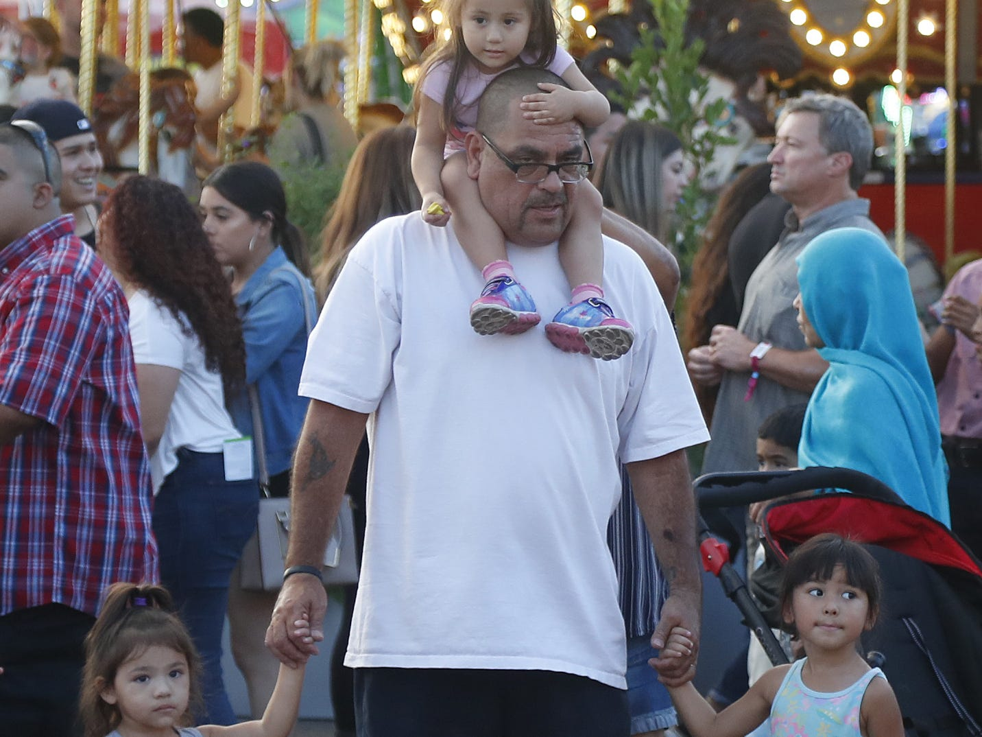 Ernie Garibay walks with his three granddaughters, Cali Granillo (on his head), Raelyn Granillo (L) and Rosie Granillo at the Arizona State Fair in Phoenix, Ariz. on October 21, 2018.