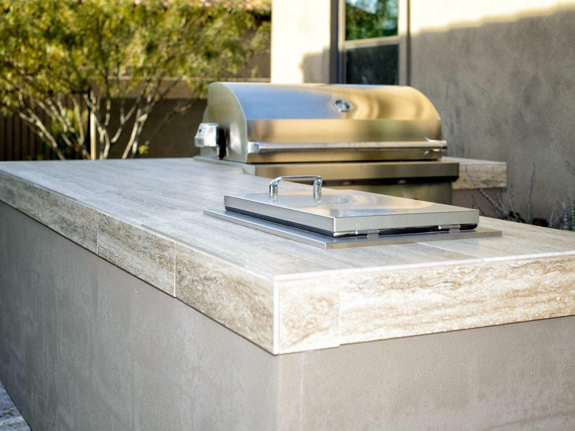 A barbecue with stainless-steel grill and drop-in cooler set in a tile top.